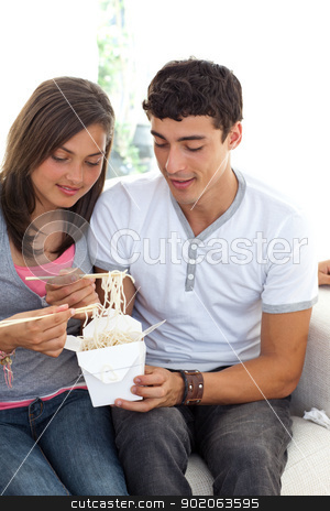 Couple of teenagers eating pasta stock photo, Couple of teenagers eating pasta at home on the sofa by Wavebreak Media