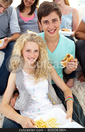 Teenagers eating burgers and fries stock photo, Teenagers eating burgers and fries on the sofa by Wavebreak Media