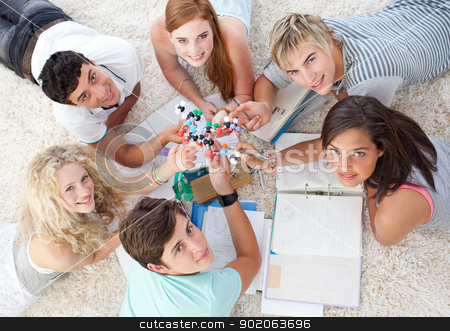 High angle of teenagers studying Science on the floor stock photo, High angle of teenagers studying Science on the floor in a house by Wavebreak Media