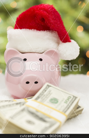 Pink Piggy Bank Wearing Santa Hat Near Stacks of Money on Snowfl stock photo, Pink Piggy Bank Wearing Santa Hat Near Stacks of Hundreds of Dollars of Money on Snowflakes. by Andy Dean
