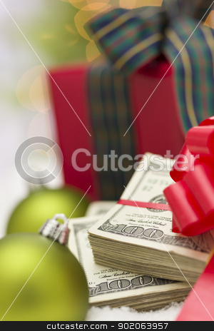 Stack of Hundred Dollar Bills with Bow Near Christmas Ornaments stock photo, Stack of One Hundred Dollar Bills with Red Bow Near Green Christmas Ornaments and Wrapped Gift Box on Snow Flakes. by Andy Dean