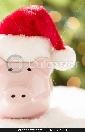 Pink Piggy Bank with Santa Hat on Snowflakes stock photo, Pink Piggy Bank Wearing Red and White Santa Hat on Snowflakes with Abstract Green and Golden Background. by Andy Dean