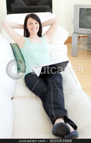 Cute woman surfing the internet lying on a sofa stock photo, Cute woman surfing the internet lying on a sofa at home by Wavebreak Media