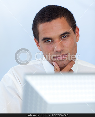 Attractive businessman working with a computer stock photo, Attractive businessman working with a computer in office by Wavebreak Media