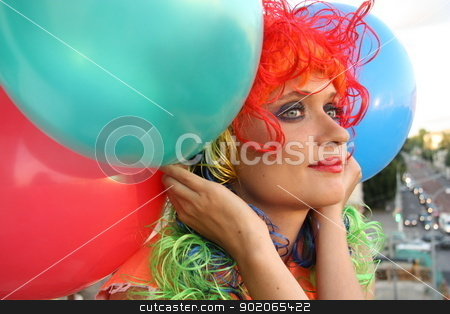 Girl in colorful wig with balloons stock photo, Beautiful Girl with multicolor hair and balloons dreaming looking over the city by Yulia Zhukova