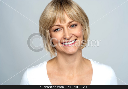 Portrait of a smiling middle aged caucasian woman stock photo, Portrait of a smiling middle aged caucasian woman isolated against grey background. by Ishay Botbol
