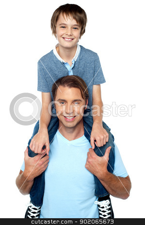 Adorable young son enjoying piggyback ride stock photo, Cheerful son enjoying a piggyback ride on his father's shoulder. Studio shot. by Ishay Botbol