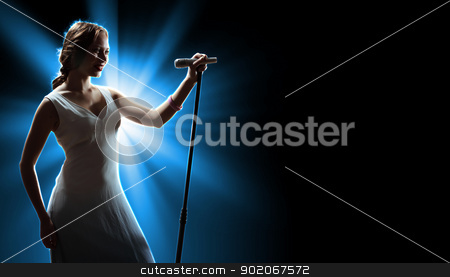 Female singer on the stage stock photo, Female singer on the stage holding a microphone by Sergey Nivens