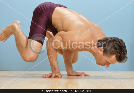 Mayurasana yoga position stock photo, Fit male athlete performs a mayurasana yoga position on floor by Chad Zuber