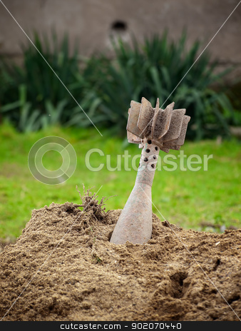 Unexploded grenade stock photo, Unexploded mortar shell stuck in the ground. by Sinisa Botas