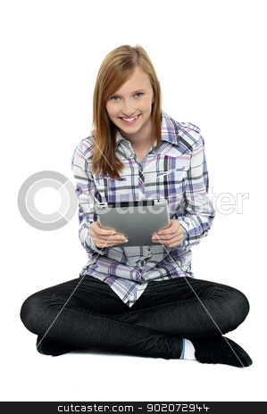 Smartly dressed teenager surfing on tablet pc stock photo, Smartly dressed teenager surfing on tablet pc. Sitting with legs crossed on studio floor. by Ishay Botbol