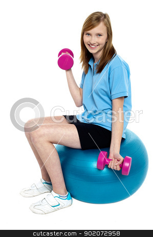 Pretty teen seated on a blue pilate ball doing dumbbells stock photo, Pretty teen seated on a blue pilate ball doing dumbbells. Stay fit and healthy. by Ishay Botbol