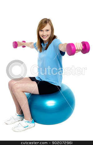 Girl sitting on pilates ball and doing dumbbells stock photo, Girl sitting on pilates ball and doing dumbbells isolated over white background. by Ishay Botbol