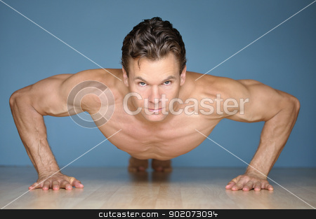 Pushup stock photo, Handsome muscular man looks at camera while performing pushup on floor with blue wall background by Chad Zuber