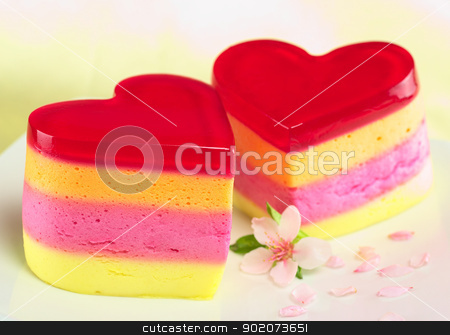 Peruvian Jelly Cake stock photo, Colorful Peruvian heart-shaped jelly-pudding cakes called Torta Helada with a peach blossom on the plate (Selective Focus, Focus on the three upper lines on the front of the left cake) by Ildiko Papp