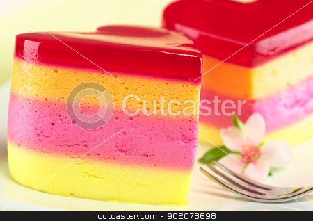 Peruvian Jelly Cake stock photo, Colorful Peruvian heart-shaped jelly-pudding cakes called Torta Helada with a peach blossom and a fork on the plate (Selective Focus, Focus on the front surface of the left cake) by Ildi Papp