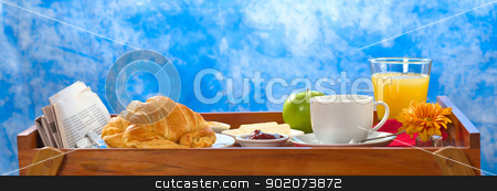 Breakfast Tray stock photo, Delicious breakfast on tray consisting of coffee, orange juice, apple, croissants, jam and butter with newspaper lying on the side by Ildi Papp