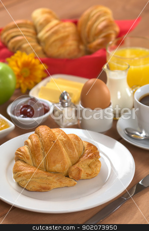 Continental Breakfast stock photo, Delicious continental breakfast consisting of coffee, milk, orange juice, croissant, boiled egg, jam, butter and apple (Selective Focus, Focus on the front of the croissant) by Ildiko Papp