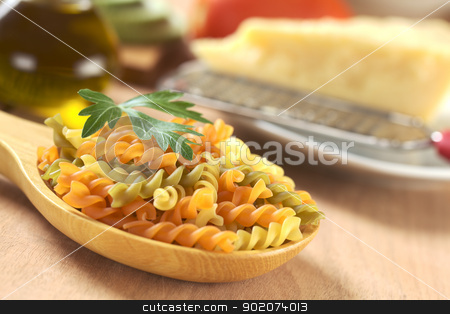 Raw Fusilli Pasta stock photo, Colorful raw fusilli pasta on wooden spoon and garnished with a parsley leaf, with cheese and oil in the back (Very Shallow Depth of Field, Focus on the tip of the leaf and the and the orange fusilli in front of it) by Ildiko Papp