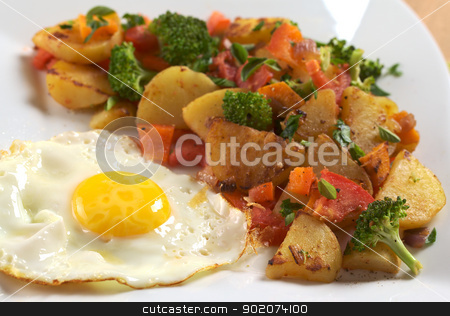 Fried Egg and Fried Potatoes stock photo, Fried egg with fried potatoes, broccoli, carrot, tomato and onion and seasoned with fresh oregano (Selective Focus, Focus on the egg yolk and the front of the fried vegetables) by Ildiko Papp