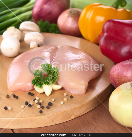 Raw Chicken Breast  stock photo, Raw chicken breast with white and black pepper corns, parsley leaf and garlic surrounded by fresh vegetable (Selective Focus, Focus on the front of the meat, the garlic and the parsley) by Ildiko Papp
