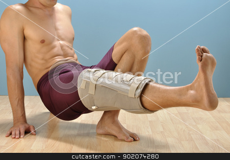 Injury therapy stock photo, Male athlete with leg injury does leg lift exercise to strengthen leg by Chad Zuber