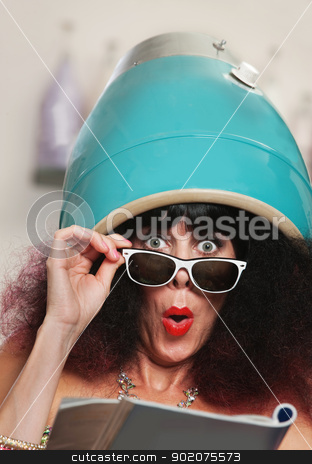 Woman Reading Under Hair Dryer stock photo, Surprised female reading magazine while under hair dryer by Scott Griessel