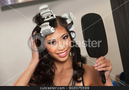 Smiling Asian Woman with Mirror stock photo, Smiling young woman in curlers holding mirror  by Scott Griessel