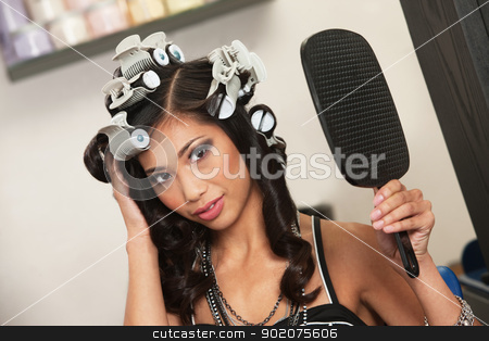 Woman Admiring Her Hairdo stock photo, Beautiful Vietnamese lady with hair curlers and mirror by Scott Griessel