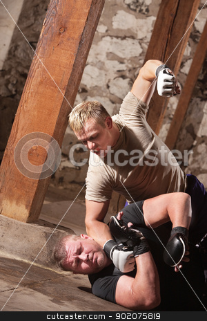MMA Fighter Beating Opponent stock photo, Blond male MMA fighter strikes opponent on the ground by Scott Griessel