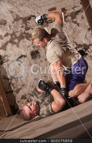 Two MMA Fighters On The Floor stock photo, Man punching pinned opponent on the ground by Scott Griessel