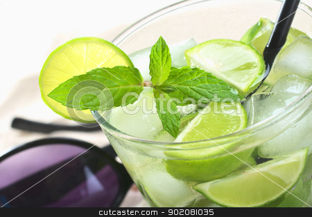 Mojito Cocktail stock photo, Mojito cocktail made of white rum, ice cubes, sugar, mint leaves and limes with a black drinking straw and sunglasses in the back (Selective Focus, Focus on the front of the mint leaf)  by Ildiko Papp