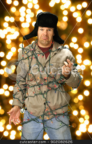 Christmas lights stock photo, Funny confused man wrapped in colorful Christmas lights by Chad Zuber