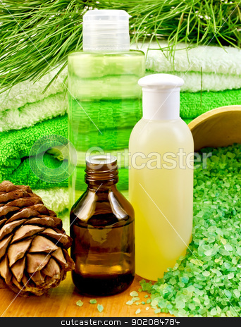 Oil and Gel with cedar cones stock photo, Cedar oil in a bottle, branch of cedar cones, towels and salt in a wooden bowl, lotion, shower gel on a wooden board by rezkrr