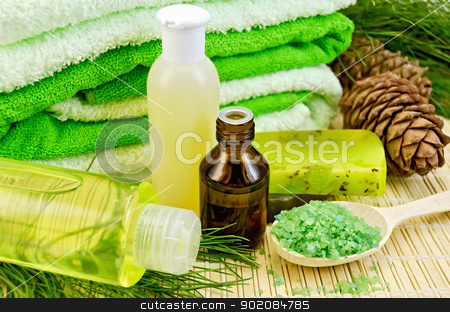 Oil and toiletries with cedar cones stock photo, Oil in a bottle, cedar cones with branch, two green homemade soap, towels, salt in the wooden spoon, lotion, shower gel on a bamboo mat by rezkrr