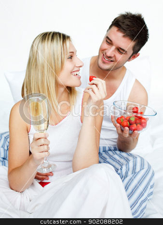 Lovers celebrating an engagement with strawberries and champagne stock photo, Lovers celebrating an engagement with strawberries and champagne in bed by Wavebreak Media