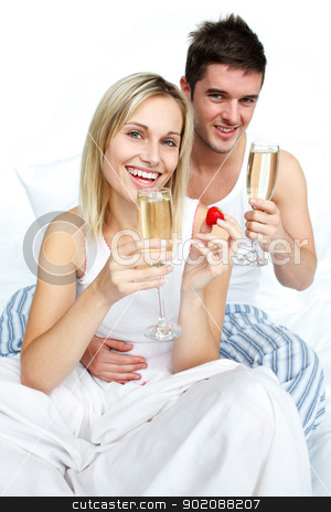 Happy man and woman celebrating an engagement with champagne stock photo, Happy man and woman celebrating an engagement with strawberries and champagne in bed by Wavebreak Media