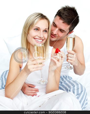 Young lovers eating strawberries and drinking champagne stock photo, Young lovers eating strawberries and drinking champagne in bed by Wavebreak Media