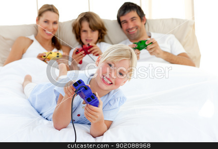 Little blond girl playing video game with her family stock photo, Little blond girl playing video game with her family in the bedroom by Wavebreak Media