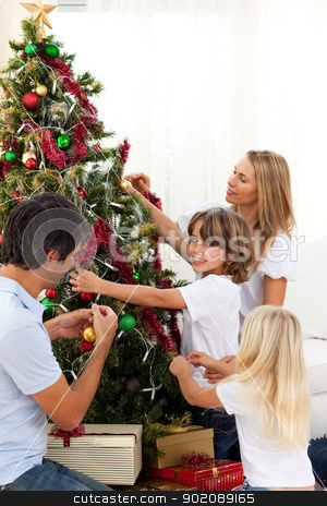 Happy family decorating Christmas tree stock photo, Happy family decorating Christmas tree at home by Wavebreak Media