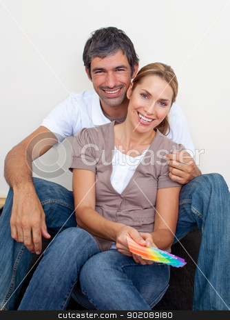 Couple choosing color to paint their new house stock photo, Smiling couple choosing color to paint their new house by Wavebreak Media