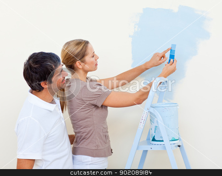 Happy couple painting together stock photo, Happy couple painting together in their new house by Wavebreak Media
