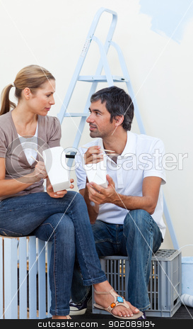Couple eating while renovating their new house  stock photo, Young couple eating while renovating their new house  by Wavebreak Media