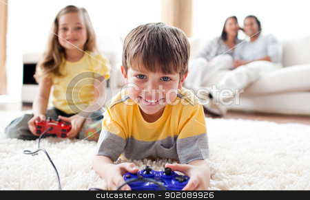 Cute little boy playing video game with his sister  stock photo, Cute little boy playing video game with his sister lying on the floor by Wavebreak Media