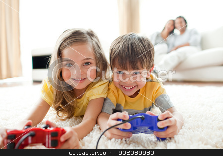 Loving siblings playing video game stock photo, Loving siblings playing video game in the living room by Wavebreak Media