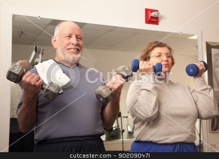 Senior Adult Couple Working Out in the Gym stock photo, Active Senior Adult Couple Working Out in the Gym. by Andy Dean