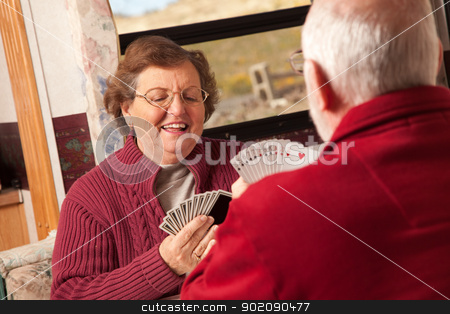 Happy Senior Adult Couple Playing Cards in Their Trailer RV stock photo, Happy Senior Adult Couple Playing Cards in Their Travel Trailer RV. by Andy Dean