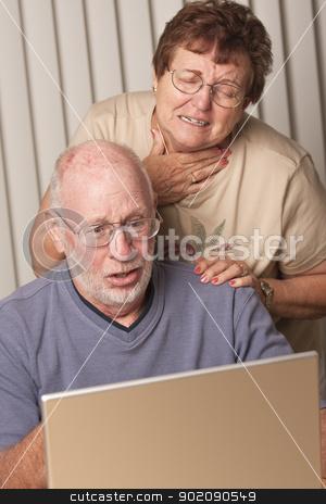 Smiling Senior Adult Couple Having Fun on the Computer stock photo, Smiling Senior Adult Couple Having Fun on the Computer Laptop Together. by Andy Dean