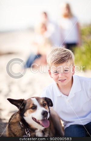 Handsome Young Boy Playing with His Dog stock photo, Handsome Young Boy Playing with His Dog at the Beach.  by Andy Dean