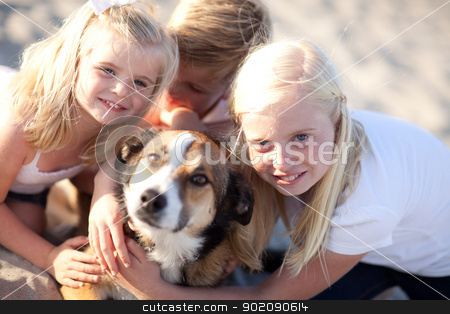 Cute Sisters and Brother Playing with Dog stock photo, Cute Sisters and Brother Playing with Dog at the Beach. by Andy Dean
